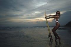 Woman in bikini with her surfboard stock image