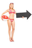 Woman in bikini holding a beach ball and an arrow Royalty Free Stock Photos
