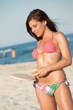 Woman in bikini holding a beach racket Stock Photos