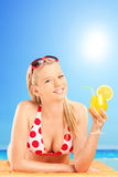 Woman in bikini holding a cocktail on a beach Royalty Free Stock Images