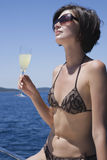 Woman In Bikini Holding Drink While Relaxing On Deck Royalty Free Stock Photos