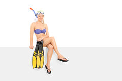 Woman in bikini holding flippers seated on a panel Royalty Free Stock Photos