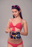 Woman in bikini holding many colourful sunglasses Royalty Free Stock Photo