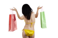 Woman in bikini holding souvenir bags Royalty Free Stock Images