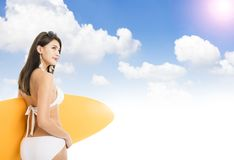 Woman in bikini and holding surfboard with cloud background Stock Images