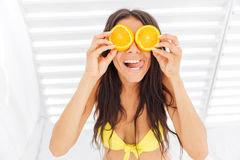 Woman in bikini holding two halves of orange against eyes. Funny cheerful young woman in bikini holding two halves of orange against her eyes over white stock images
