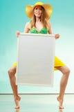 Woman in bikini holds blank presentation board. Royalty Free Stock Image