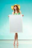 Woman in bikini holds blank presentation board. Royalty Free Stock Photo
