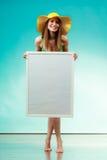 Woman in bikini holds blank presentation board. Royalty Free Stock Photography