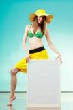 Woman in bikini holds blank presentation board. Stock Image