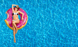 Woman in bikini on the inflatable mattress in the swimming pool. Royalty Free Stock Photography