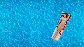 Woman in bikini on the inflatable mattress in the swimming pool. Royalty Free Stock Photos