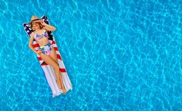 Woman in bikini on the inflatable mattress in the swimming pool. Royalty Free Stock Photo