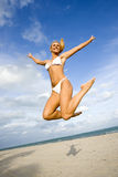 A woman in a bikini jumping on a beach Royalty Free Stock Images