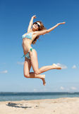 Woman in bikini jumping on the beach Stock Photos