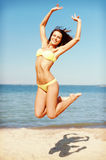 Woman in bikini jumping on the beach Royalty Free Stock Photo