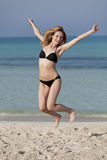 Woman with bikini jumping happily on the beach portrait Stock Image