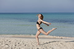 Woman with bikini jumping happily on the beach portrait Royalty Free Stock Photos