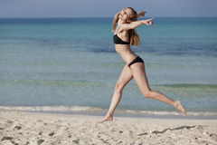 Woman with bikini jumping happily on the beach portrait Royalty Free Stock Photography