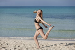 Woman with bikini jumping happily on the beach portrait Stock Images