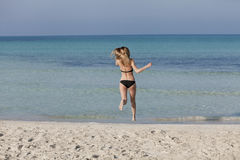 Woman with bikini jumping happily on the beach portrait Stock Photo