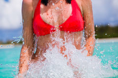 Woman in bikini jumping out of the water Royalty Free Stock Photos
