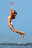 Woman in bikini jumps out of water Stock Photography