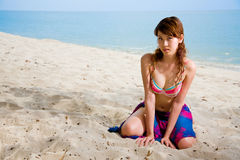 Woman in bikini kneelingon the beach Stock Photography