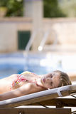 Woman in bikini laying with eyes closed poolside on lounge chair Royalty Free Stock Photography