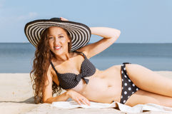 Woman in bikini lying down and sunbathing on the beach Royalty Free Stock Images