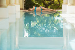 Woman In Bikini Lying By Swimming Pool Royalty Free Stock Photography