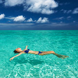 Woman in bikini lying on water Stock Photos