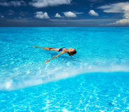 Woman in bikini lying on water. At tropical beach Stock Photography