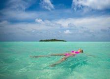 Woman in bikini lying on water at tropical beach.  Stock Photo