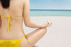 Woman in bikini meditating at calm beach Royalty Free Stock Images