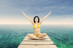 Woman in bikini meditating at shore Stock Images