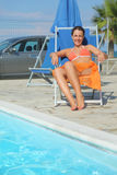 Woman in bikini and pareo sitting on beach chair Royalty Free Stock Photos