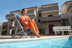 Woman in bikini and pareo sitting on beach chair Royalty Free Stock Photo