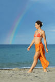 Woman in bikini and pareo walking on beach Royalty Free Stock Images