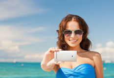 Woman in bikini with phone Stock Images