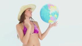 Woman in a bikini playing with a earth ball stock footage