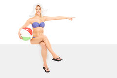 Woman in bikini pointing right seated on a panel Royalty Free Stock Image