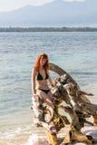 Woman in bikini posing on branchy log in water Stock Photo