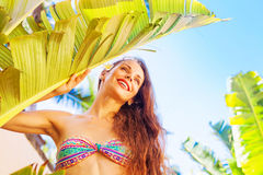 Woman in bikini posing near the palm tree leaf. Happy woman in bikini posing near the big tropical palm tree leaf Stock Images