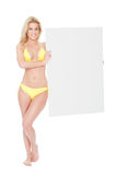 Woman in bikini presenting empty board Royalty Free Stock Images