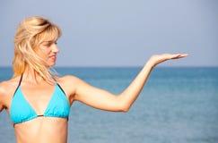 Woman in bikini presenting the sea vacation. Attractive woman in bikini presenting the sea vacation Royalty Free Stock Photos