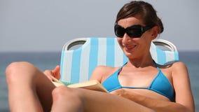 Woman in bikini reading book stock footage