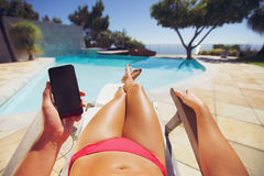 Woman in bikini reclining on chair with phone Royalty Free Stock Image