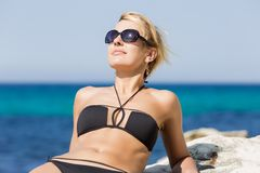 Woman in bikini reclining on rock leaning on her elbows. Rest by the sea. Waist up portrait of blond woman in black bikini and tinted sunglasses reclining on royalty free stock images