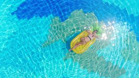 Woman in bikini relaxes on inflatable mattress in a pool.